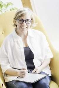 Irmgard Wallner sitzt am gelben Sessel und schreibt